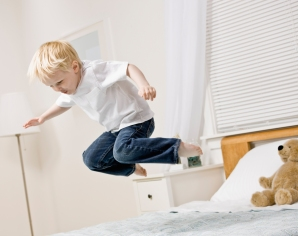 Mischievous boy jumping in mid-air on bed in bedroom